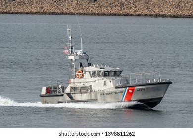 Fairhaven, Massachusetts, USA - May 15, 2019: 47-foot motor lifeboat Menemsha heading into New Bedford with hurricane barrier in background