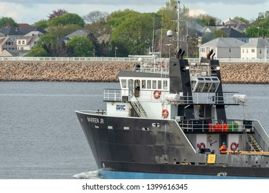 Fairhaven, Massachusetts, USA - May 15, 2019: Offshore supply vessel Warren Jr, hailing port Cape May, New Jersey, leaving Fairhaven with New Bedford hurricane barrier in background