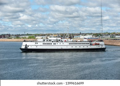 Fairhaven, Massachusetts, USA - May 15, 2019: Ferry Nantucket leaving Fairhaven with New Bedford hurricane barrier in background
