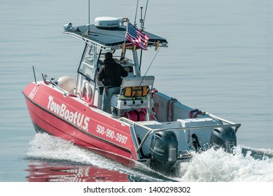 Fairhaven, Massachusetts, USA - May 16, 2019: Commercial tow boat digs a hole as it  accelerates toward Buzzards Bay on windless morning