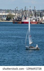 Fairhaven, Massachusetts, USA - May 8, 2019: Small sailboat under sail in light wind in New Bedford harbor