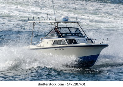 Fairhaven, Massachusetts, USA - September 3, 2019: Small cabin cruiser sending up spray as she cuts through wake of passing ferry