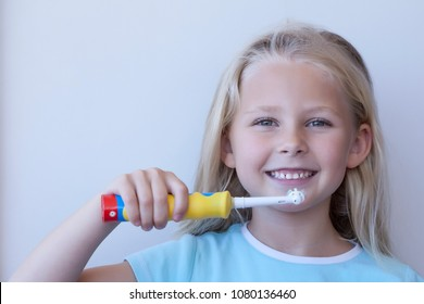 A fair-skinned girl with blonde hair brushes her teeth with a toothbrush. Image is isolated on white background. There is room for your text. Hygiene of the oral cavity. Daily hygiene. Eletrical tooth