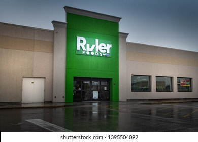 Fairview Heights, IL--May 11, 2019; front entrance of Ruler Foods discount grocery store, a Kroger banner brand, reflects off of water in parking lot on rainy day in southern Illinois.