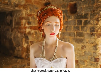 Fairy edwardian redhead princess with freckles in the old castle. Fabulous rococo queen against backdrop of stone wall. Edwardian doll. Fairy princess in palace. Many freckles on face
