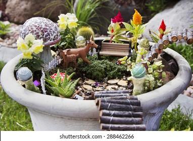 Fairy garden with deer, gazing balls and mushrooms in a flower pot