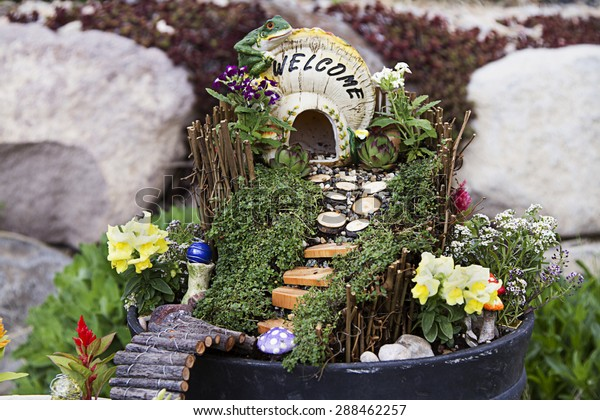 Fairy garden with a house made of a mushroom with a path and stairs in a flower pot