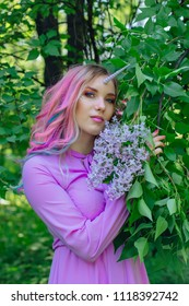 Fairy girl unicorn with rainbow hair and shiny makeup holding lilac flowers.
