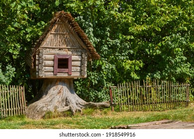 Fairy Hut of Grandmother Yaga Standing on Chicken Legs and covered with green foliage of trees