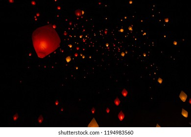 Fairy illuminated paper lanterns flying in a black sky