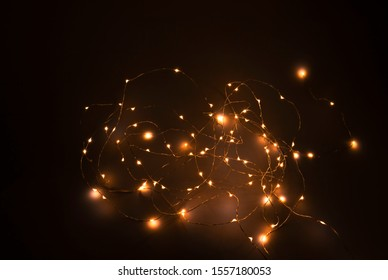 Fairy light in a tangle on a black background at night.