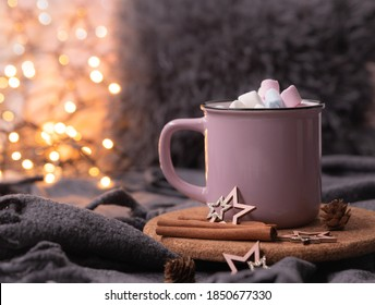 Fairy lights background, hot cocoa with marshmallows, pink cup, cinnamon sticks, cones, soft plaid blanket for cozy atmosphere at home during Christmas and New Year holidays. Soft focus bokeh.
