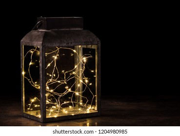 fairy lights inside vintage lantern on wooden table