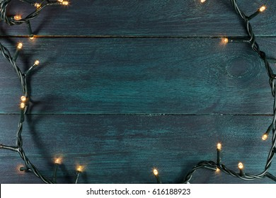 Fairy Lights On A Dark Wooden Texture Holiday Background With Place For Text