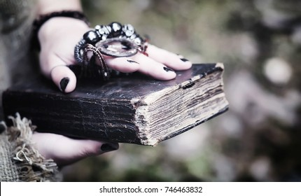 Fairy magician. A sorcerer with a glass sphere, a magical spell and a ritual. Elder with a staff and a cross in the forest. Black and white magic. A spell in old book.