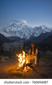 Fairy Meadows, Pakistan - October 4, 2017: A Pakistani man was sitting near the bonfire at Fairy Meadows, Pakistan. The background is Nanga Parbat mountain.