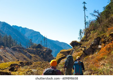 Fairy Mountain Landscape in Nepal Country Himalayas layered Hills Forest and Moss capped Stones and group of Hikers walking rear View