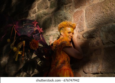 fairy in orange dress at a castle wall