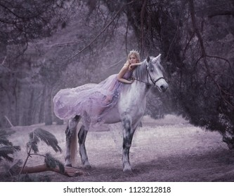 A fairy in a purple, transparent dress with a long flying train lies on a unicorn. Sleeping Beauty. Blonde girl walking with pegasus in the forest. The Elven Song. Artistic processing.
