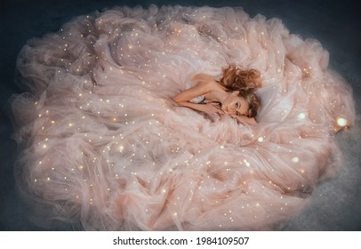 Fairy queen fashion model in luxurious shining pink dress posing in studio. Princess girl, peach outfit with sequins lies in fabrics of outfit, long skirt gown. Fantasy woman sleeping beauty woke up