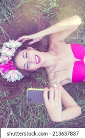 fairy selfy: filtered image of beautiful brunette young lady in pink bikini and flower crown having fun making selfie picture lying on green grass outdoors copy space background
