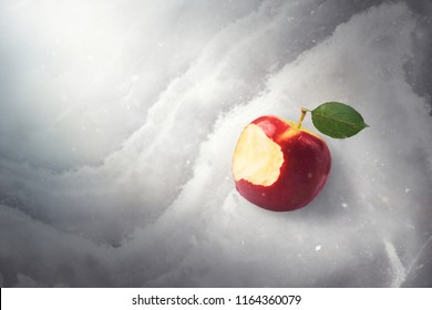 Fairy tale tale concept with poisoned bitten red apple laying on marble, sunlight and defocused falling snow, top view, high quality image. Once upon a time.