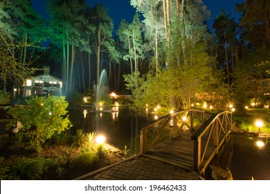 Fairy tale cottages by the lake in the conifer forest at night