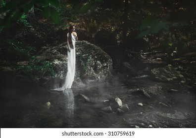 Fairy tale. Female person in a mystical garden pensively looking down