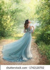 fairy tale princess in light summer blue, turquoise dress standing in park. Happy Woman walks towards wind. fashion model posing. fantasy image girl goddess. flying long hem of dress. nymph of forest