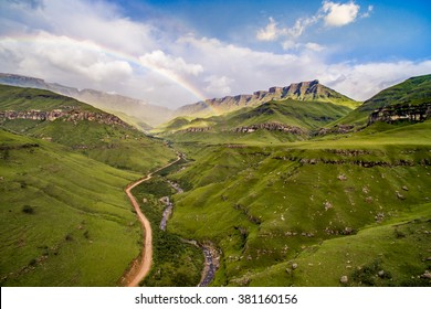 Fairy tale stunning rainbow over very wide valley called Sani Pass at South Africa and Lesotho border, with the offroad road and wild river and green meadows, with the rocks on the horizont