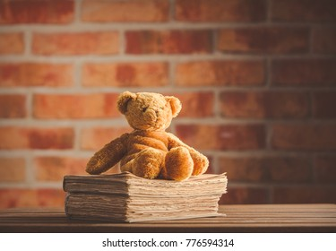 Fairy tale teddy bear and old books on wooden table at brick wall background. Library