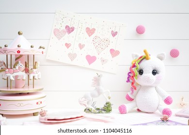 Fairy tales concept in pink and white. Cute macarons of mermaid and unicorn. Top view. Selective focus on the unicorn crochet plush animal doll.