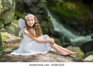 Fairy with wings in front of a waterfall, magical fantasy