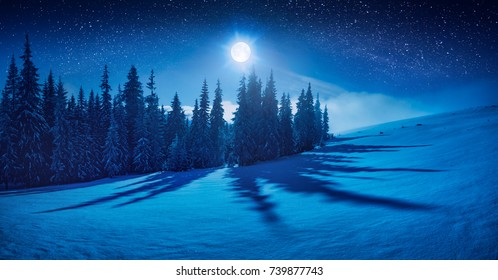 Fairy winter night in a mountain valley with full moon in a starry sky. Christmas mood.