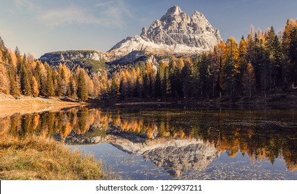 Fairytale Antorno lake and Famous peak of Tre Cime di Lavaredo under  sunlight during Sunset. Scenic image of Stunning nature in Dolomites alps. Amazing Autumn Landscape. popular travel location.