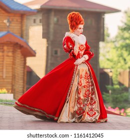 Fairytale countess in castle. Young baroque redhead queen with historical hairsdo. Renaissance princess with red hair. Fairytale queen in red gown with collar. Baroque countess with rococo hairdo