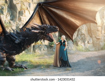 fairytale girl with white hair with warm blue clothes stands near rocks, strong powerful awesome black dragon, mythological animal with large wings, sun glare