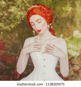 Fairytale hero. Renaissance redhead princess with hairstyle in castle. Fabulous rococo queen in white dress against the backdrop of old stone wall. Doll in the corset. Fairytale princess in palace
