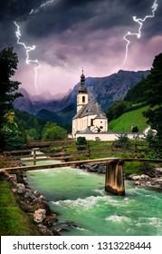 Fairytale mountain church along the river while lightning strikes thunderstorm at ramsau, bavaria, berchtesgaden