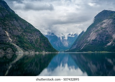 Fairytale norwegian fjord landscape. Mirror water and mountain range at typical north cloudy day. Eidfjord, Hordaland, Norway.
