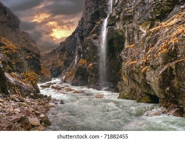 Fairytale river at sunset in a valley with rapid current and a small waterfall from a steep mountain