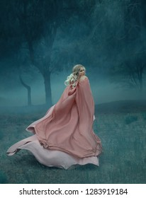 fairy-tale witch with blond hair who runs in a dark and dense mysterious forest full of white mist, dressed in a long, flying and flowing peach rosewood dress and raincoat, woman in the moonlight
