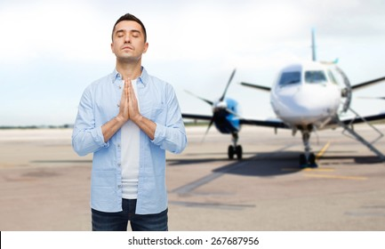faith in god, hope and people concept - happy man with closed eyes praying over airplane on runway background