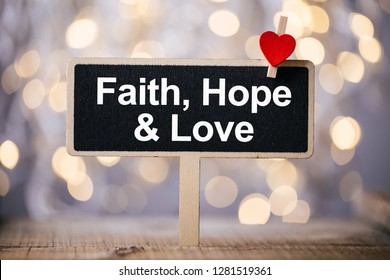 Faith Hope And Love blackboard with red heart against beautiful shiny background.