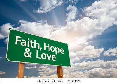 Faith, Hope and Love Green Road Sign with Dramatic Clouds, Sun Rays and Sky.
