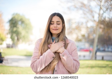 Faithful woman closes eyes and keeps hands on chest near heart, shows her kindness or favour, expresses sincere emotions, being kind hearted and honest. Body language and real feelings concept