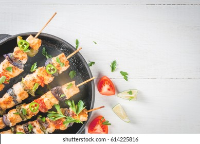 Fajita chicken kebabs, with chicken meat, pepper, chili, tomatoes, onions, lime juice and herbs. In a frying pan, on a white wooden table. Mexican cuisine, a traditional food, Top view, copy space
