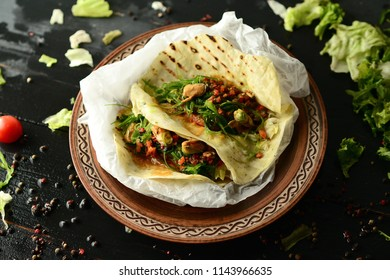 Fajitas (Mexican burritos) with meat, greens and cherry tomatoes on a wooden board