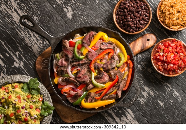 Fajitas in skillet with side dishes.