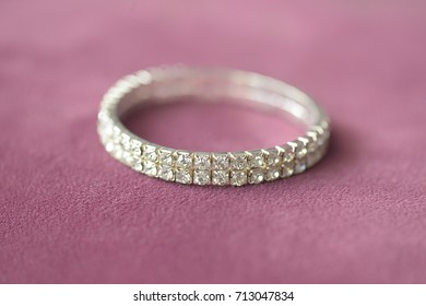 Fake diamonds double row prong setting mount bracelet with selective focus, positioned on a dusky pink suede cloth